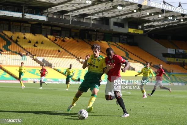 Norwich City's German-born Swiss defender Timm Klose challenges Manchester United's Nigerian striker Odion Ighalo during the English FA Cup...