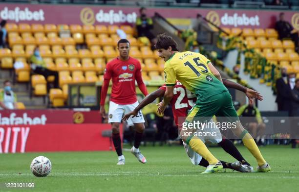 Norwich City's German-born Swiss defender Timm Klose fouls Manchester United's Nigerian striker Odion Ighalo and is sent off during the English FA...