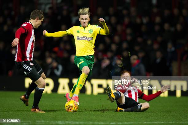Norwich City's James Maddison evades the challenge of Brentford's Andreas Bjelland and Brentford's Ryan Woods during the Sky Bet Championship match...