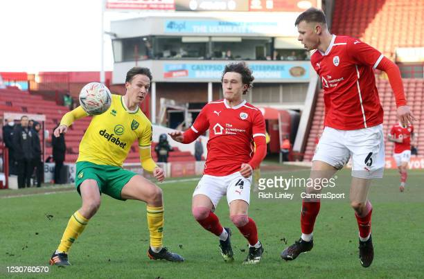 Norwich City's Kieran Dowell vies for possession with Barnsley's Callum Styles and Mads Juel Andersen during the The Emirates FA Cup Fourth Round...