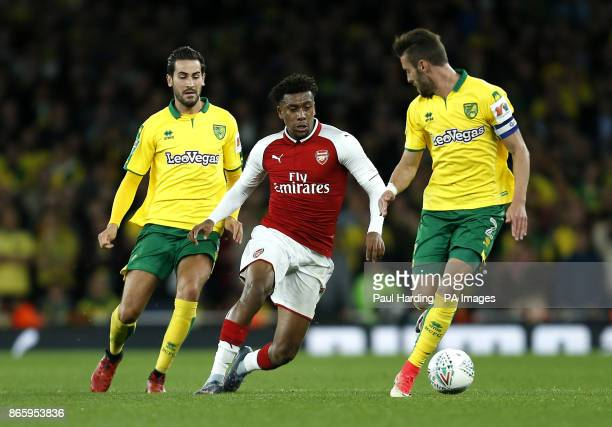Norwich City's Mario Vrancic and Daniel Ivo Pinto battle for the ball with Arsenal's Alex Iwobi during the Carabao Cup Fourth Round match at the...