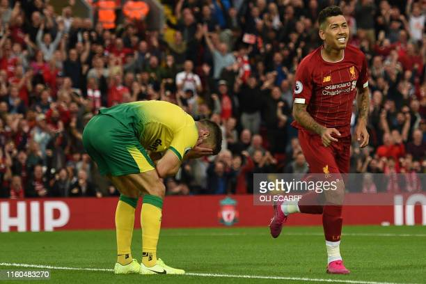 Norwich City's Scottish defender Grant Hanley reacts after scoring an own goal as Liverpool's Brazilian midfielder Roberto Firmino celebrates the...
