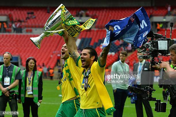 Norwich City's Scottish defender Russell Martin and Norwich City's English midfielder Bradley Johnson celebrate with the trophy after the official...