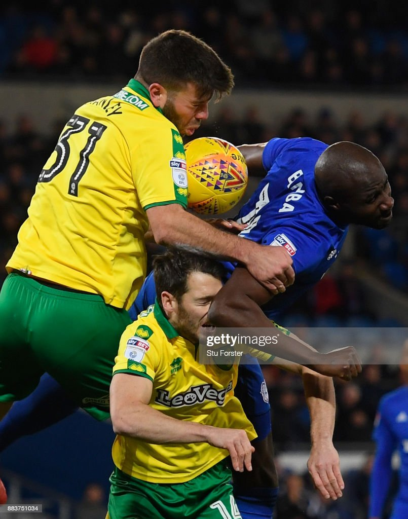 Norwich defender Grant Hanley (l) and Wes Hoolahan (c) challenge Sol Bamba of Cardiff during the Sky Bet Championship match between Cardiff City and Norwich City at Cardiff City Stadium on December 1, 2017 in Cardiff, Wales.