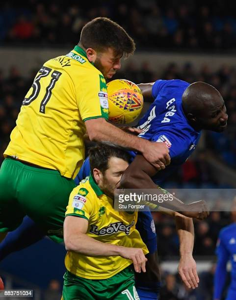 Norwich defender Grant Hanley and Wes Hoolahan challenge Sol Bamba of Cardiff during the Sky Bet Championship match between Cardiff City and Norwich...