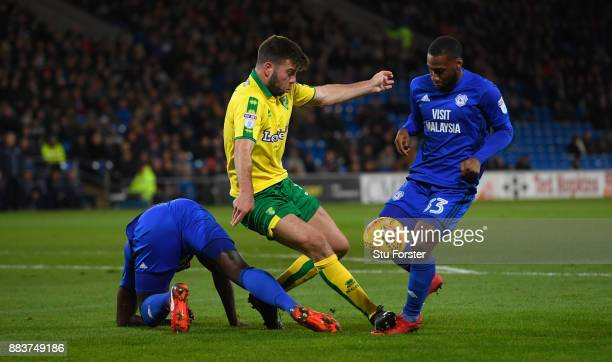 Norwich defender Grant Hanley challenges Sol Bamba and Junior Hoilet of Cardiff during the Sky Bet Championship match between Cardiff City and...