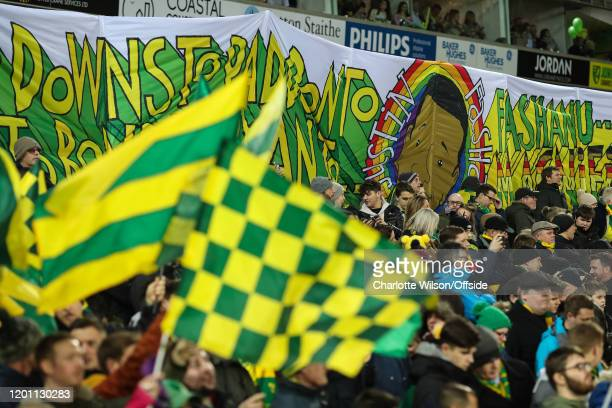 Norwich fans wave flags as they hold up a Justin Fashanu banner during the Premier League match between Norwich City and Liverpool FC at Carrow Road...