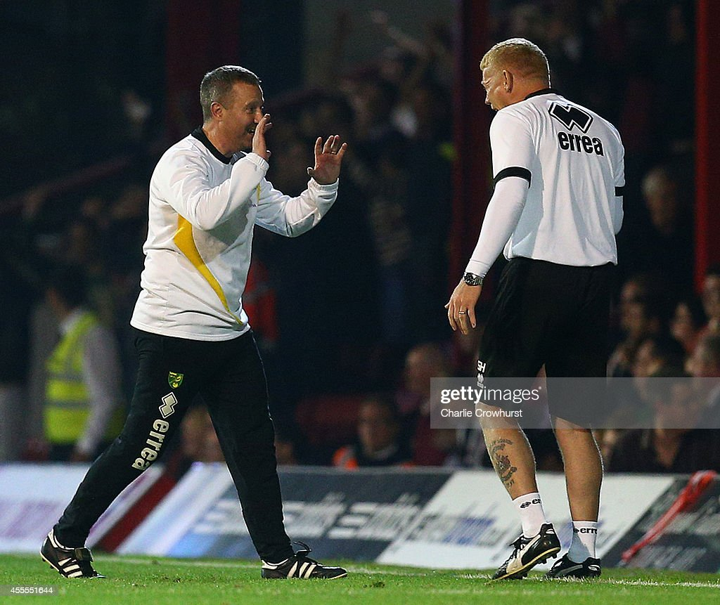 Norwich manager Neil Adams (R) celebrates the teams third goal during the Sky Bet Championship match between Brentford and Norwich City at Griffin Park on September 16, 2014 in Brentford, England.