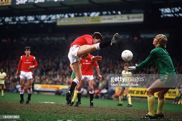 Norwich v Manchester United - Norman Whiteside raises his boot as he challenges City goalkeeper Chris Woods for the ball.
