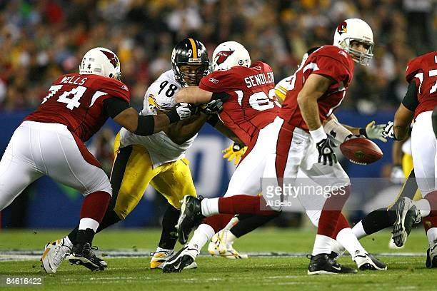 Nose tackle Casey Hampton of the Pittsburgh Steelers attempts to fight off a double team block by Reggie Wells and Lyle Sendlein of the Arizona...