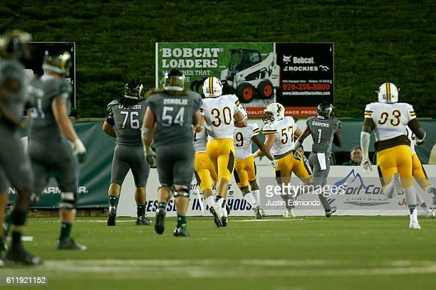 Nose tackle Chase Appleby of the Wyoming Cowboys scores a touchdown after making an interception during the second quarter against the Colorado State...