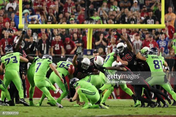 Nose tackle Corey Peters, inside linebacker Kareem Martin and cornerback Justin Bethel of the Arizona Cardinals attempt block a field goal kicked by...