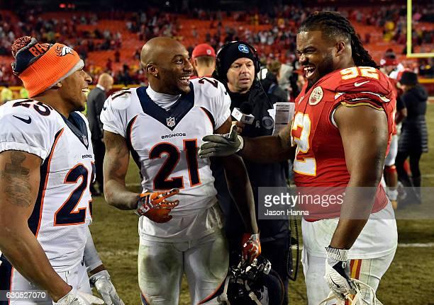 Nose tackle Dontari Poe of the Kansas City Chiefs jokes with cornerback Chris Harris and cornerback Aqib Talib of the Denver Broncos after the Chiefs...