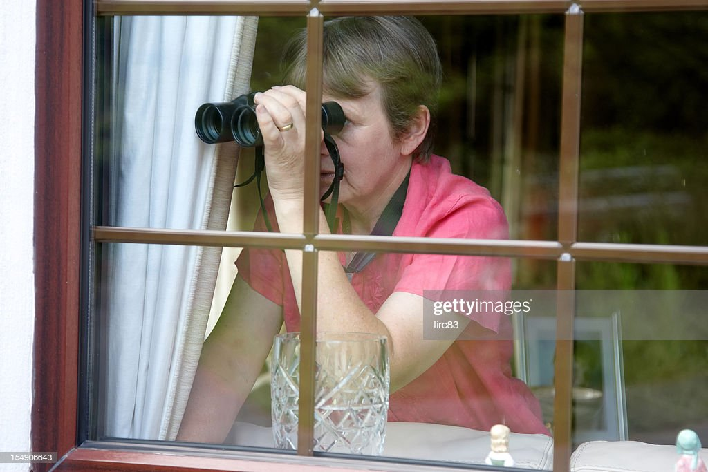 Nosey neighbour at the window with binoculars : Stock Photo