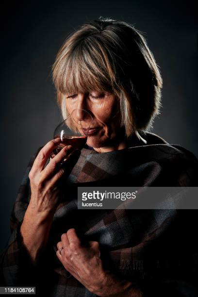 nosing a small glass of whisky - whisky stock pictures, royalty-free photos & images