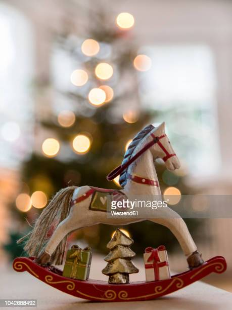 nostalgic deocrative rocking horse before a lit christmas tree - christmas still life stock pictures, royalty-free photos & images