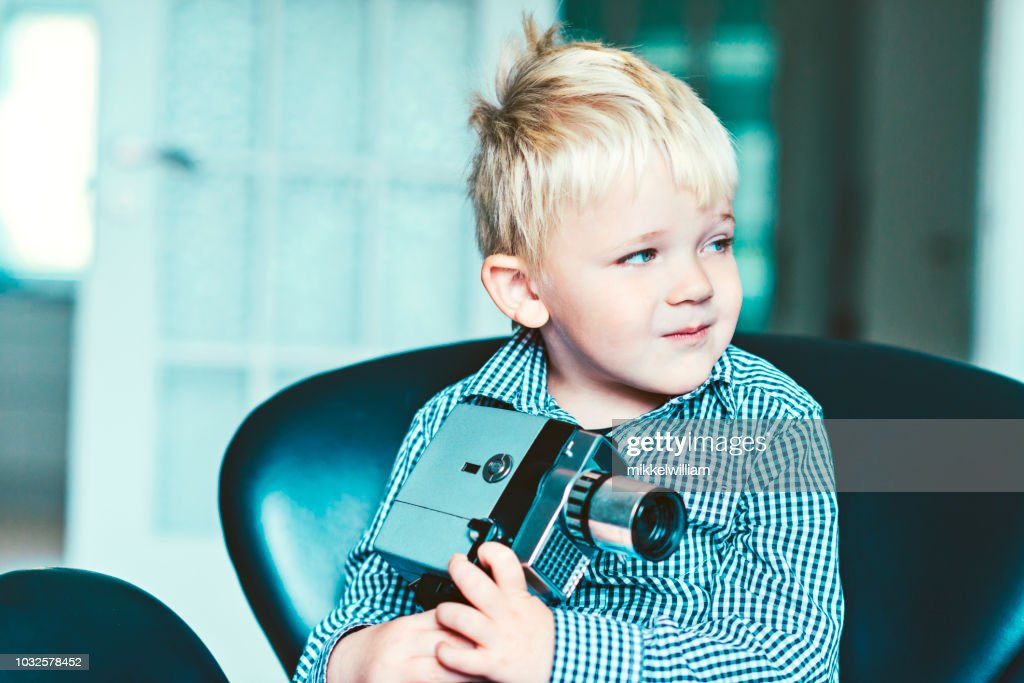 Nostalgic portrait of a kid with a retro 8mm video camera : Stock Photo