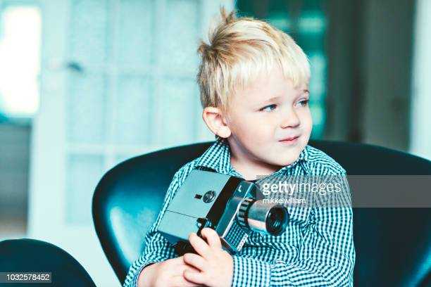 Nostalgic portrait of a kid with a retro 8mm video camera