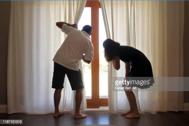 nosy couple looking out a window from behind curtain - rafael ben ari fotografías e imágenes de stock