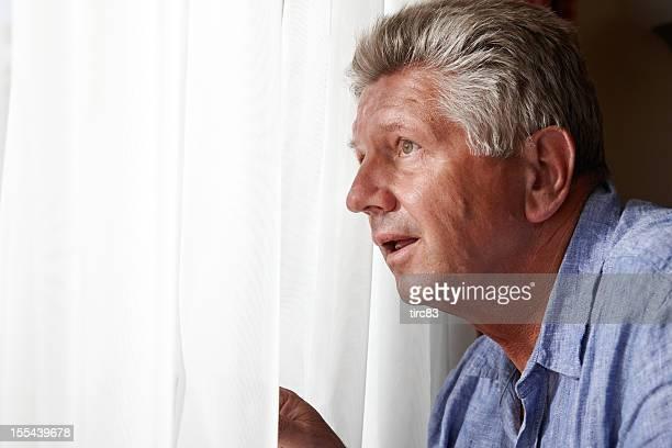 nosy hombre maduro en la ventana - entrometido fotografías e imágenes de stock