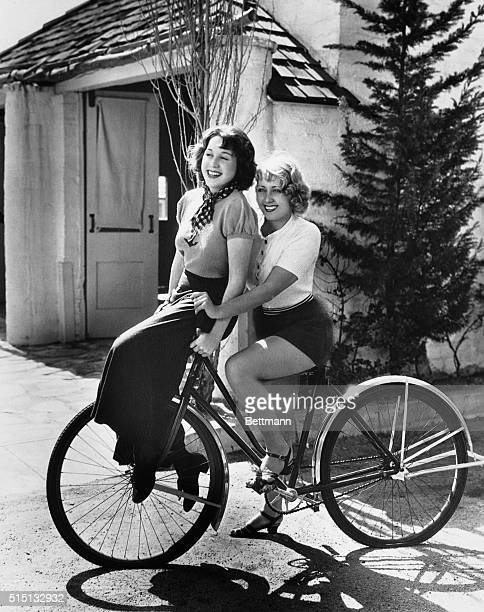 Not a bicycle built for two but Joan Blondell one of Hollywood's best known stars takes her sister Gloria for a ride on the handlebars of her bicycle