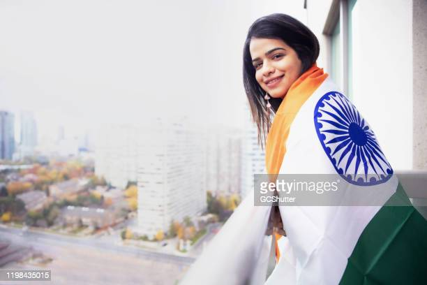 not far from my country ever! - indian girl standing at her balcony with an indian flag - republic day stock pictures, royalty-free photos & images