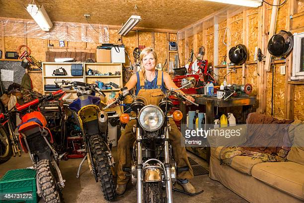 Not just for boys.  A woman in a motorcycle garage.