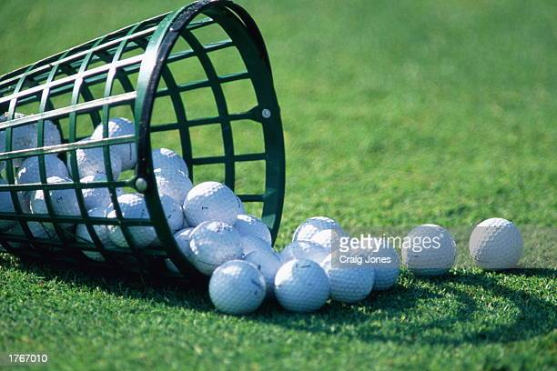 Bucket with golf balls spilling out on to lawn