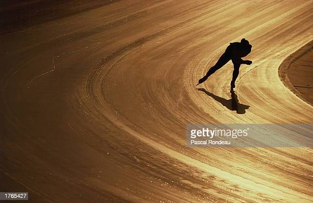 Speed skater casting shadow on track, silhouette