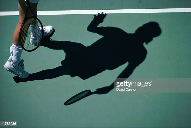 Tennis player casting shadow on court low section elevated view