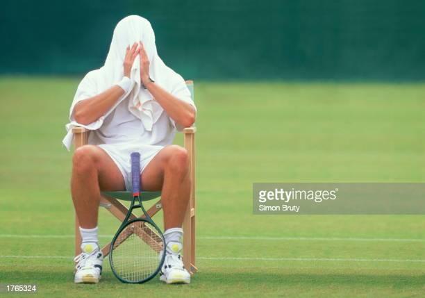 Tennis player resting between games towel covering head