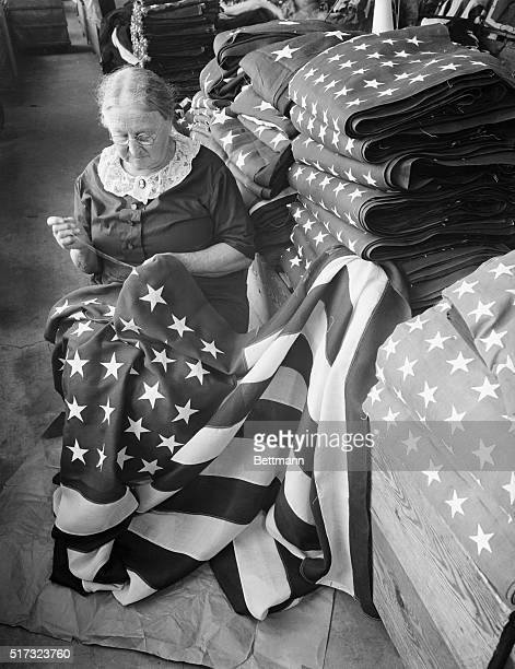 Not unlike the artist's conception of the original Betsy Ross Mary Hoffman sews the stars on a custom made flag The larger and more expensive flags...