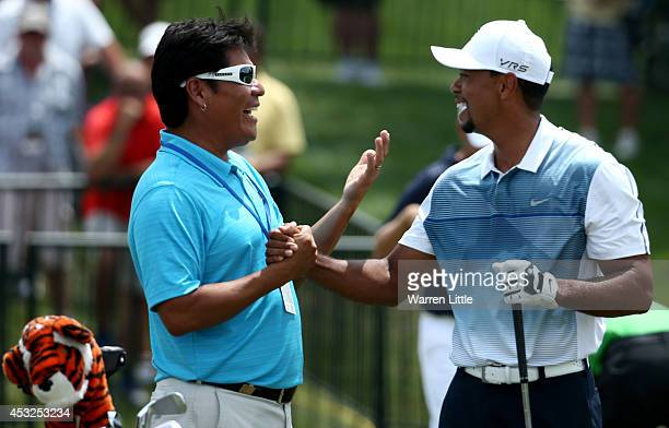 Notah Begay III and Tiger Woods of the United States shake hands on the practice range during a practice round prior to the start of the 96th PGA...