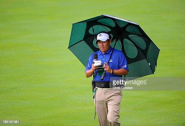 Notah Begay III of the Golf Channel shelters under an umbrella during the Day Three FourBall Matches of The Presidents Cup at the Muirfield Village...