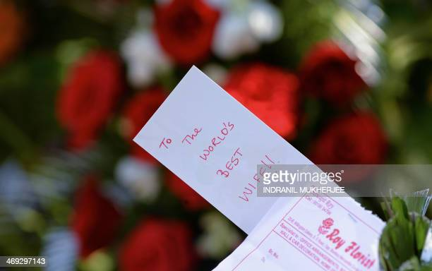 A note from a husband to his wife is seen stuck on a heart shaped flower arrangement made with roses kept for delivery at a florist's shop on...