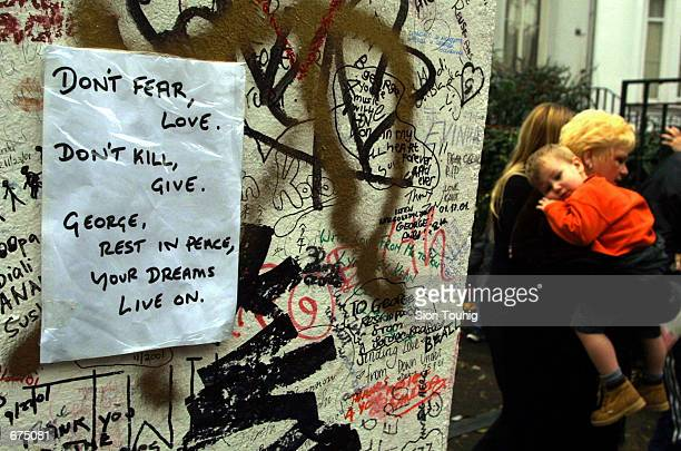 A note is attached to the wall of Abbey Road Recording Studios December 2 2001 as mourners pass by after the death of musician George Harrison An...