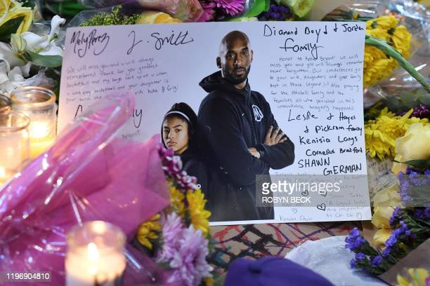 A note is seen among flowers and candles at a makeshift memorial as fans mourn the death of NBA legend Kobe Bryant who was killed along with his...