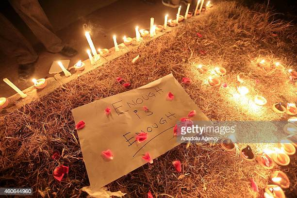 A note is seen as Pakistanis hold candle light vigil in front of the press club in Islamabad Pakistan on December 18 in memory of the victims of the...