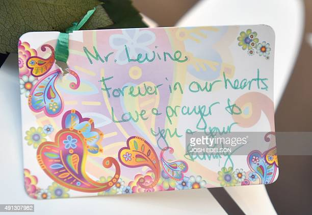 A note is seen written for professor Larry Levine one of the victims who was shot and killed at a makeshift memorial near the entrance to Umpqua...