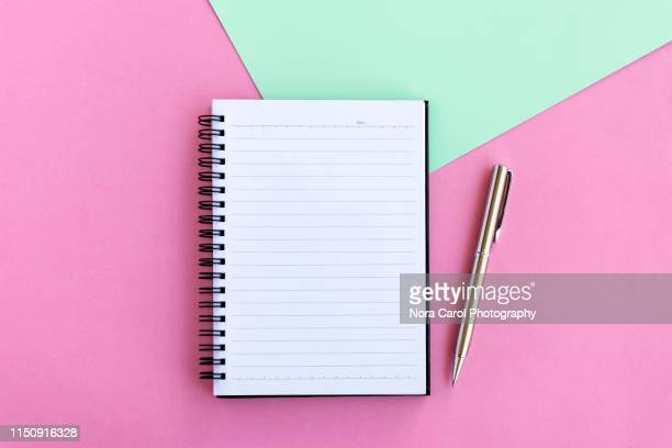 note pad and pen on pink and green background - diary stock pictures, royalty-free photos & images