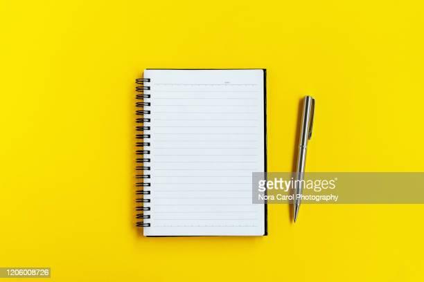 note pad and pen on yellow background - notizbuch stock-fotos und bilder