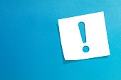 Note paper with exclamation mark on blue background