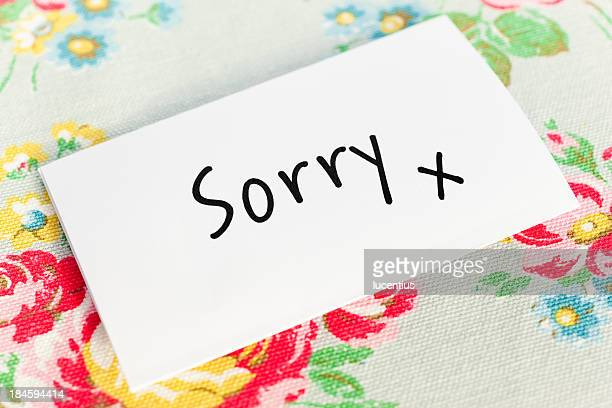 Note paper with sorry as text on table