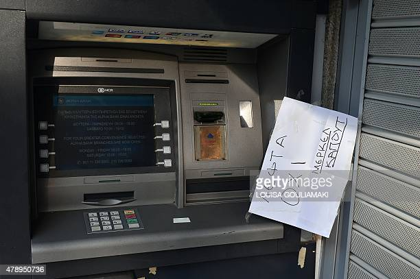 A note reading in Greek 'no moneyMerkel kaput' hangs at an Alpha bank's ATM in Athens on June 29 2015 as Greece ordered its banks to shut for one...