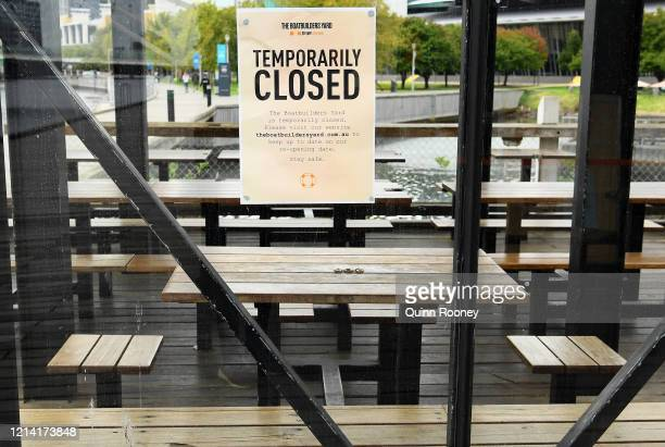 Note to customers is stuck on the window as restaurants close their businesses on March 23, 2020 in Melbourne, Australia. From midday Monday, venues...