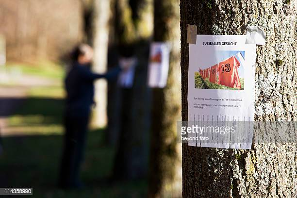 note with ad searching for football players sticking on tree