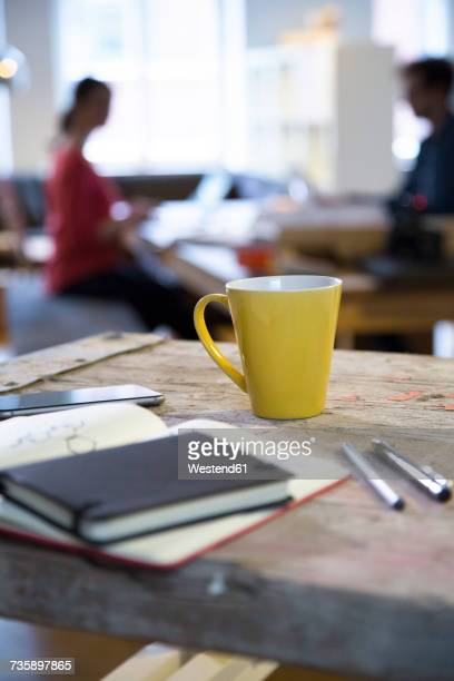 Notebook and coffee cup in modern informal office with man and woman in background