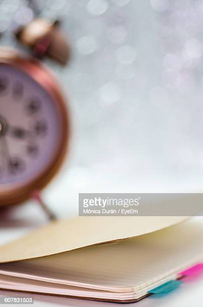 Notebook By Alarm Clock On Table