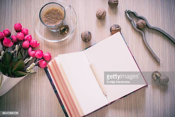 Notebook, cup of coffee and flower on wooden table