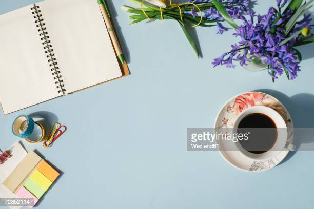 Notebook, office supplies, cup of coffee and spring flowers on light blue background